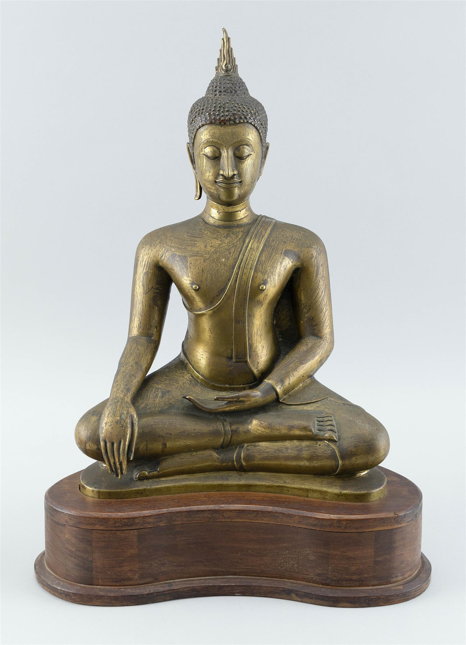"""TIBETAN GILT METAL SCULPTURE OF BUDDHA Seated in earth-touching position on a wooden base. Height 17"""". Width 12"""". Depth 7""""."""