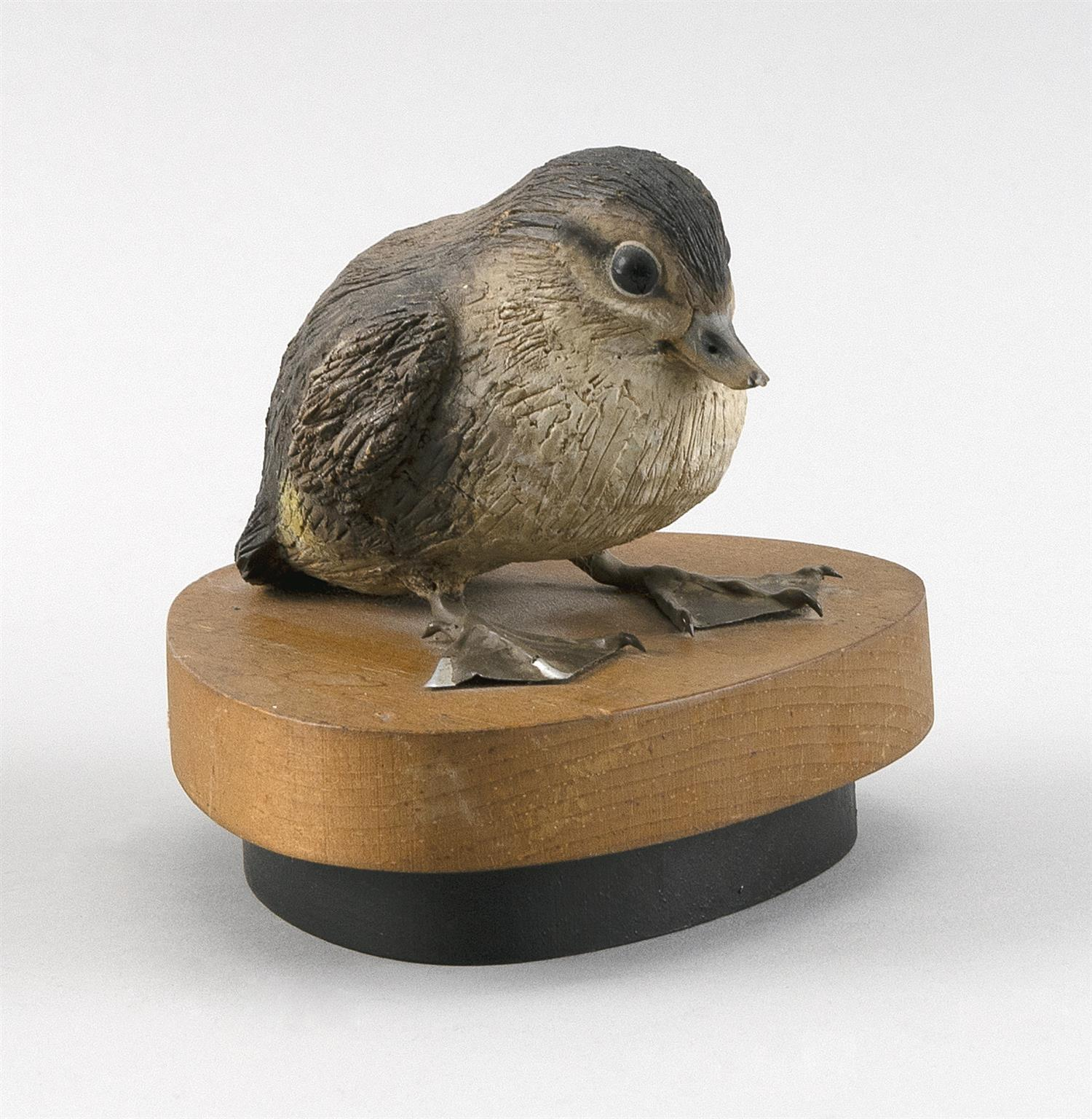 """STAN SPARRE LIFE-SIZE CARVING OF A """"3-DAY-OLD WOODY"""" BABY WOOD DUCK Mounted on a wooden base. Titled on base. Height 4""""."""