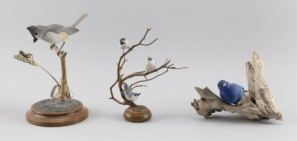 "THREE DECORATIVE BIRD CARVINGS A John Mello titmouse with grasshopper, height 9"", a Penny Wifler miniature songbird, height 7.5"", an..."
