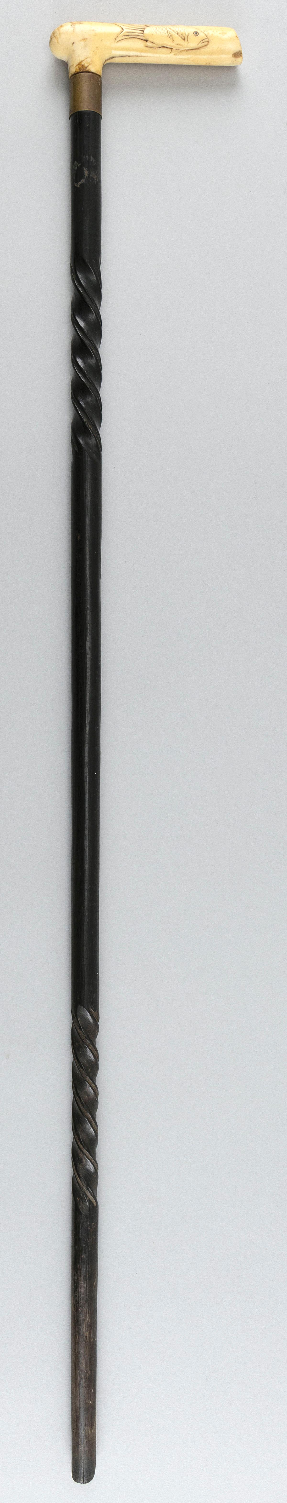 """WOODEN CANE WITH BONE HANDLE CARVED IN THE FORM OF A FISH Twist-carved shaft. Length 33""""."""