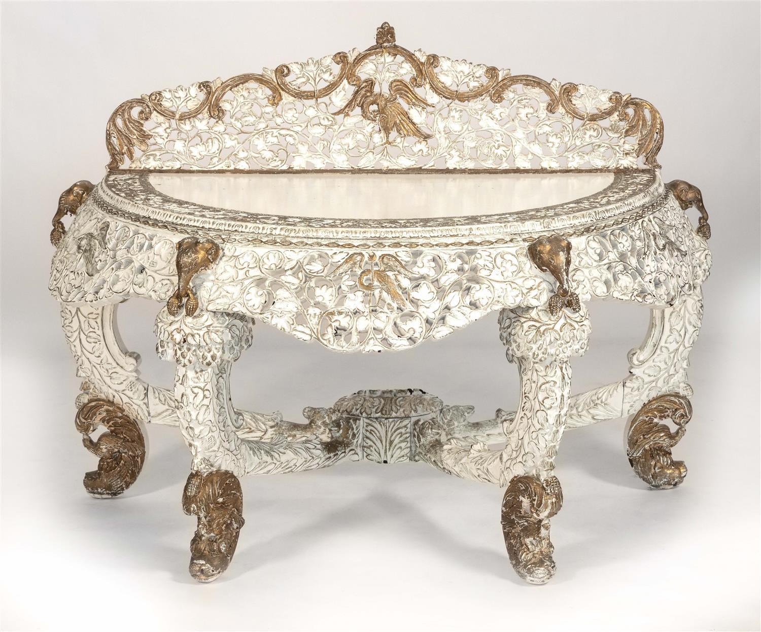 "HEAVILY AND ORNATELY CARVED DEMILUNE TABLE Painted white. Height 42"". Width 56"". Depth 29""."