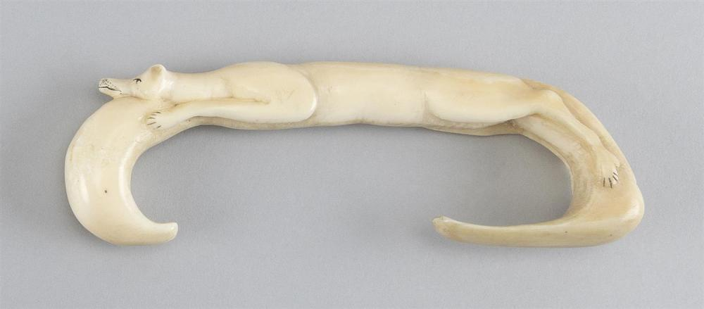 "WALRUS IVORY CARVING In the form of fox-like animal stretched out on a C shape. Engraved eyes, nose, mouth and paws. Length 6""."