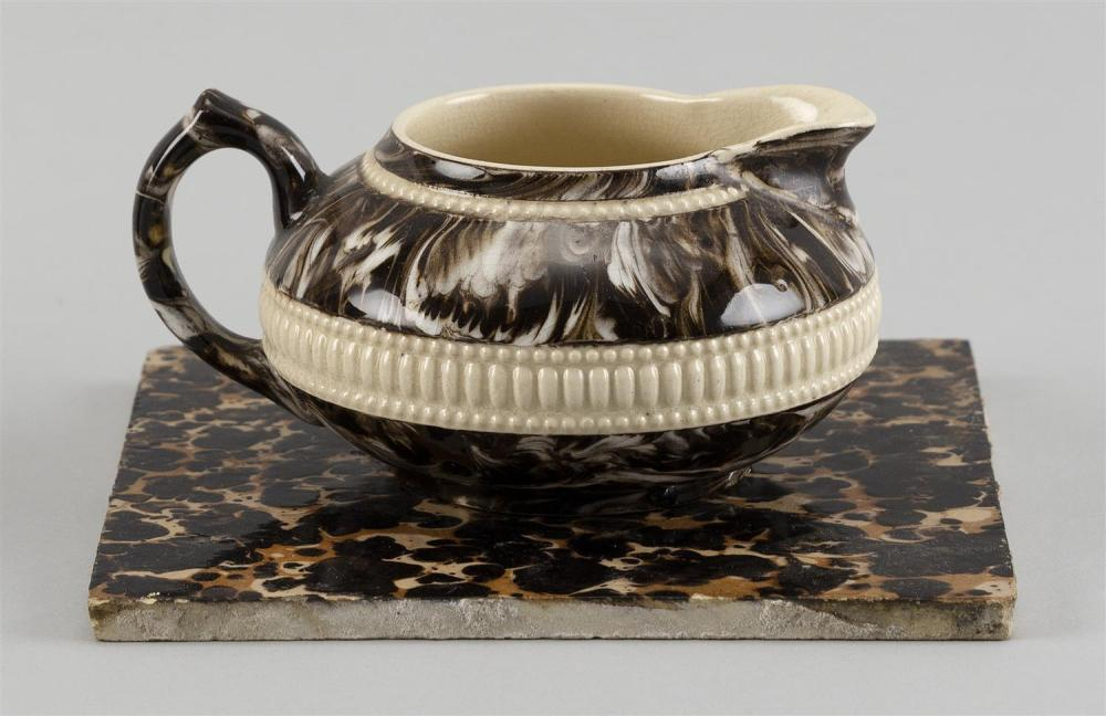 """TWO PIECES OF MOCHAWARE POTTERY A trivet, 5.25"""" x 5.25"""", and a creamer, height 2.5"""". Provenance: Jonathan Richards Collection."""