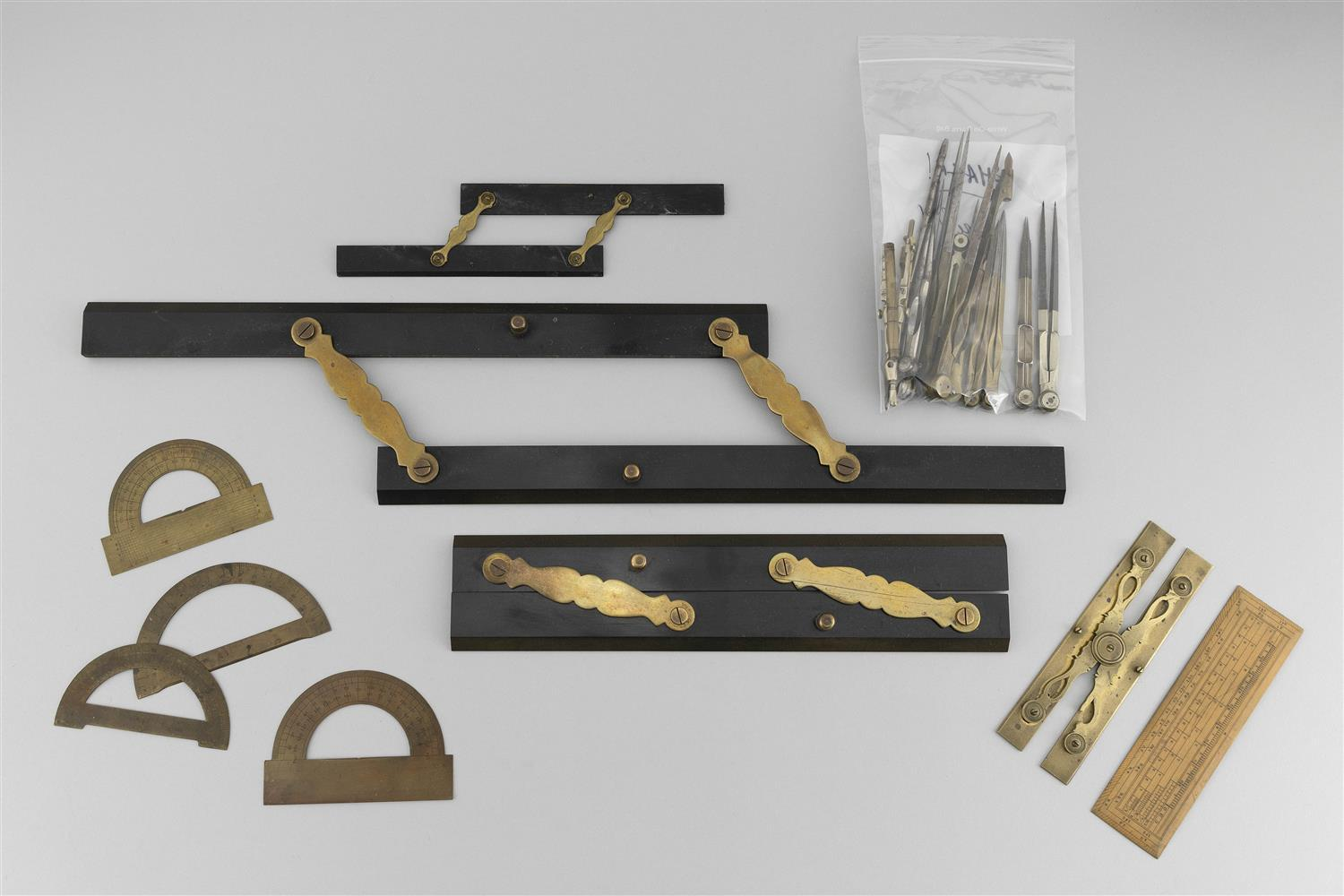 COLLECTION OF NAVIGATIONAL TOOLS AND IMPLEMENTS Includes four parallel rulers, four metal protractors, eight dividers, two drafting...