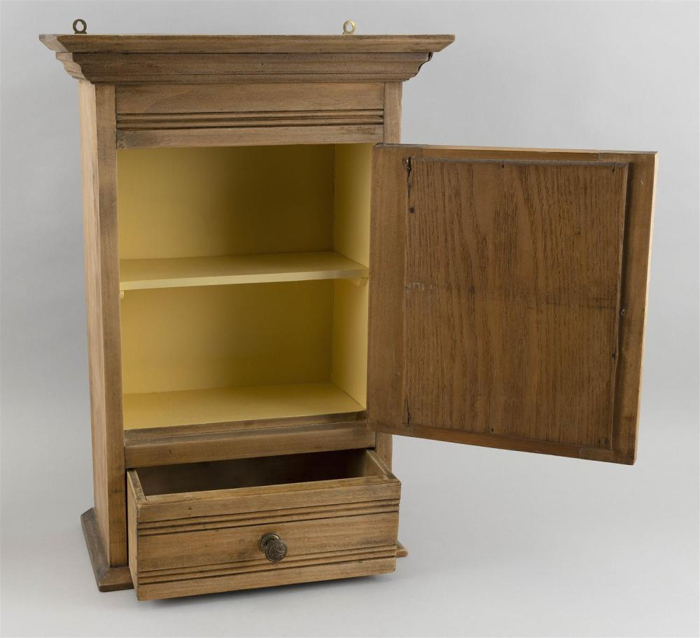SMALL HANGING CABINET In poplar under a natural finish. Paneled door with an inset mirror over a single drawer. Height 21.5