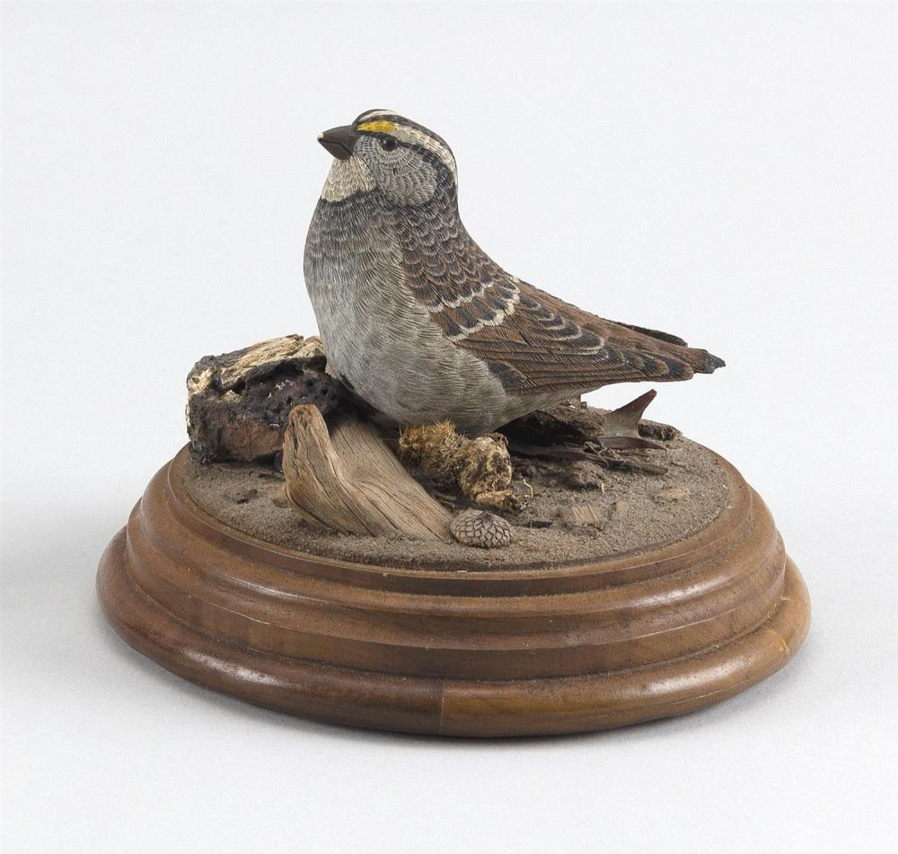 """ROBERT RIVELLO LIFE-SIZE CARVING OF A SPARROW Mounted on a circular wooden base. Signed and dated on underside. Height 5.5""""."""