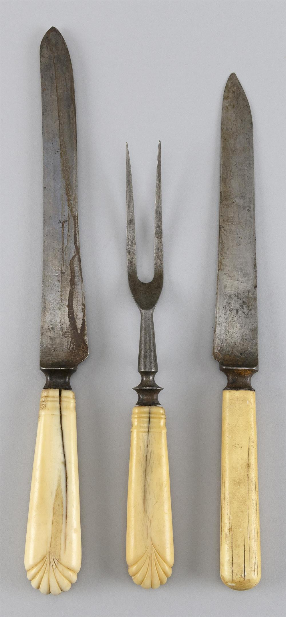 THREE-PIECE CARVING SET WITH BONE AND WALRUS IVORY HANDLES Includes two knives and a two-tine fork. One knife and fork with matching...