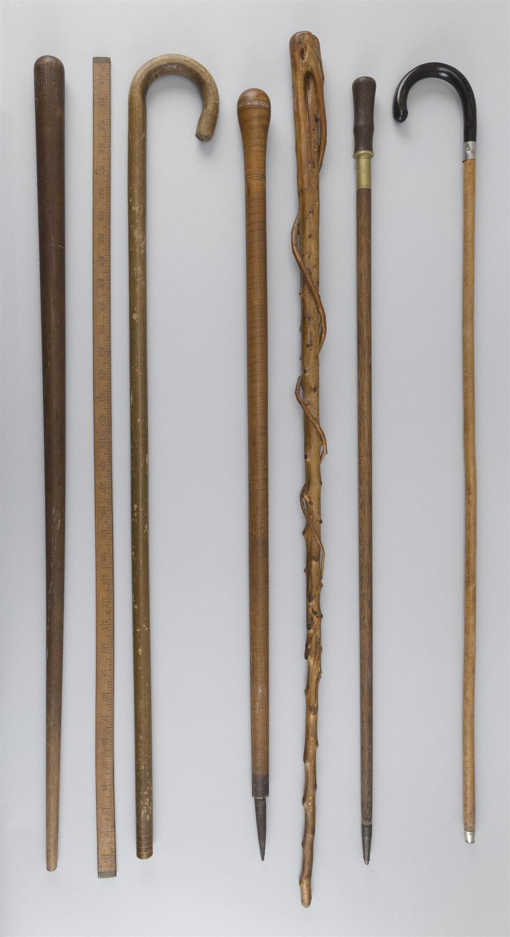 "SIX WOODEN CANES AND A YARDSTICK Lengths from 33.75"" to 39""."