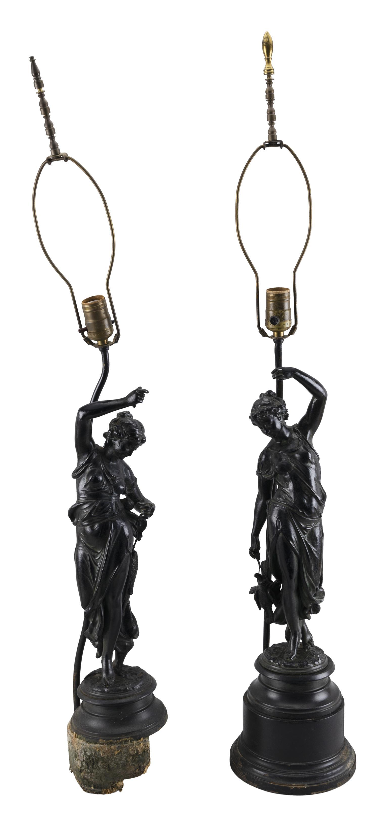 PAIR OF PAINTED METAL FIGURAL LAMPS Each in old black paint depicting a classical woman, one with game on a string, and the other mi...