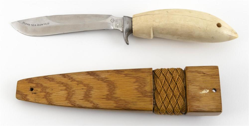 * KNIFE WITH CARVED WHALE'S TOOTH HANDLE Handle carved to resemble a fish's head. Includes wooden sheath with sailor's ropework band