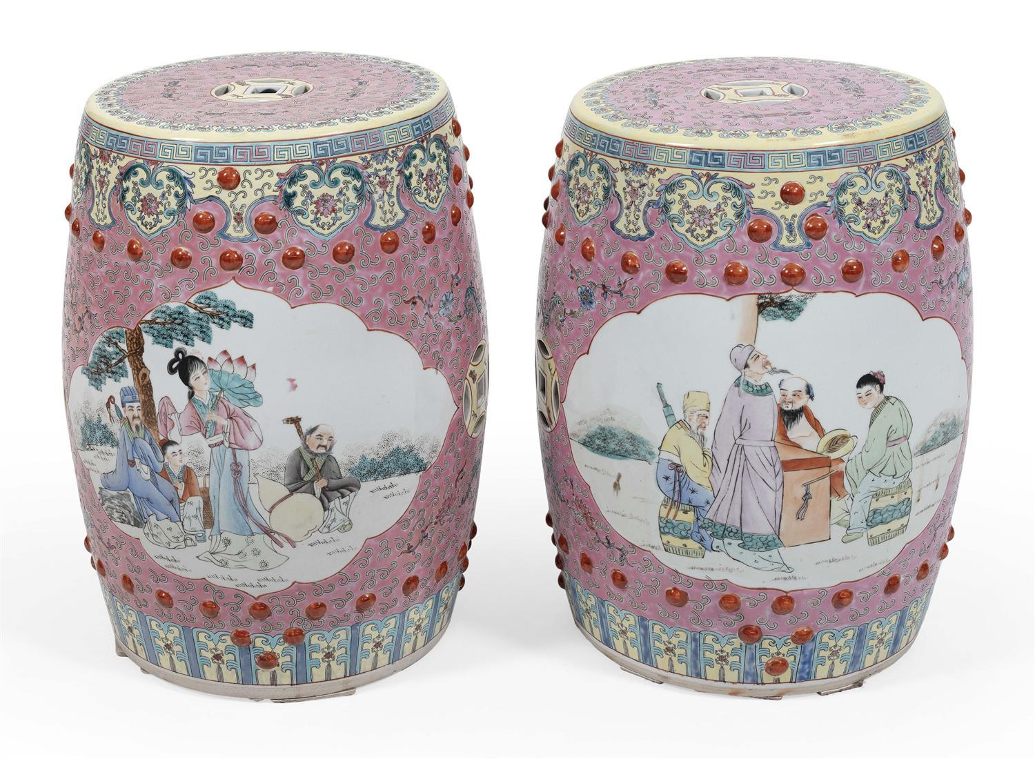 PAIR OF CHINESE FAMILLE ROSE PORCELAIN GARDEN SEATS Two figural cartouches on a vine-filled pink ground with raised bosses and famil...