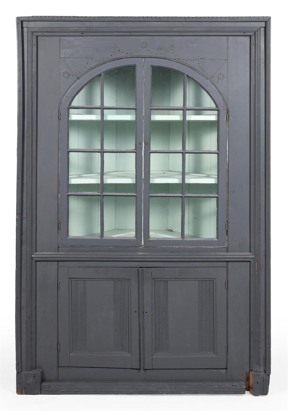ONE-PIECE CORNER CUPBOARD In pine, under gray paint. Top with sunburst carving. Upper half with two paneled glass doors enclosing tw...