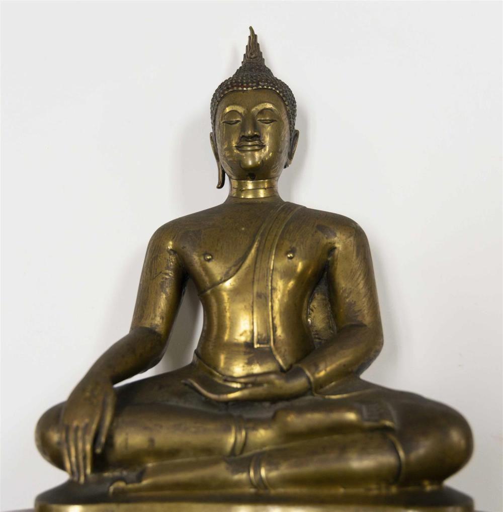 TIBETAN GILT METAL SCULPTURE OF BUDDHA Seated in earth-touching position on a wooden base. Height 17