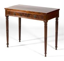ANTIQUE AMERICAN SHERATON WORK TABLE In mahogany and mahogany veneer. One drawer with brass ring pull. Turned legs end in bun feet....