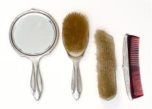 FOUR-PIECE STERLING SILVER DRESSER SET Foliate engraved and monogrammed. Includes mirror, two brushes, and a comb.