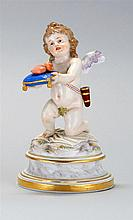 MEISSEN PORCELAIN FIGURE A cherub holding a tasseled blue pillow with a heart resting on top. Crossed swords mark on base. Height 6½...