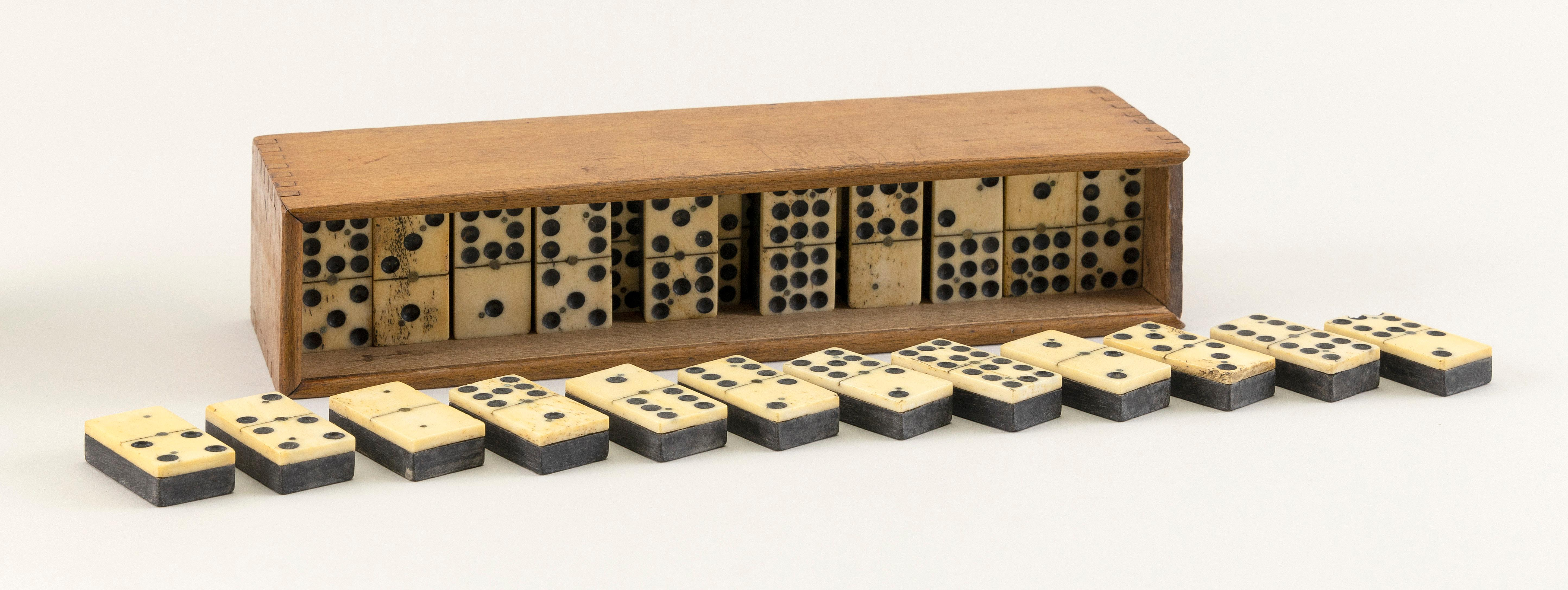 """BOXED SET OF FIFTY-FIVE BONE AND EBONY DOMINOES Late 19th/Early 20th Century Box height 3"""". Length 10.75"""". Width 2.25""""."""