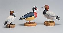THREE MINIATURE WATERFOWL CARVINGS A canvasback drake, a wood duck drake and a redhead drake, all by Peter Peltz of East Sandwich, M...