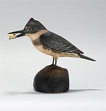 LIFE-SIZE DECORATIVE CARVED KINGFISHER By A. Elmer Crowell of East Harwich, Massachusetts. Glass eyes. Holding a carved fish in its...