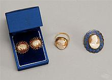 THREE PIECES OF CAMEO JEWELRY: pair of earrings with garnet surround, brooch with enamel surround, and ring in yellow gold mount.
