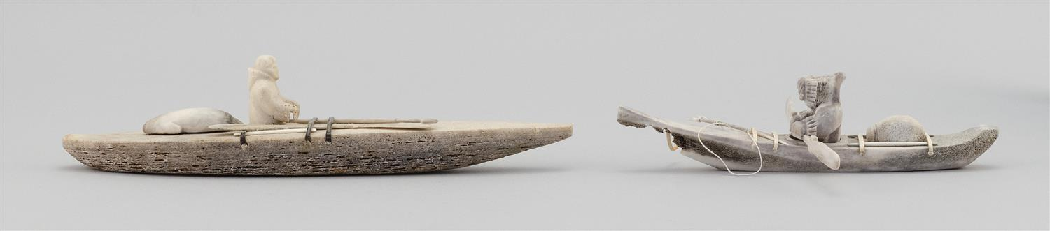 """TWO ESKIMO CARVED WHALEBONE KAYAKS Both with a seated Eskimo, harpoons and a seal. One missing paddle. Lengths 7"""" and 9.5"""". This ite..."""