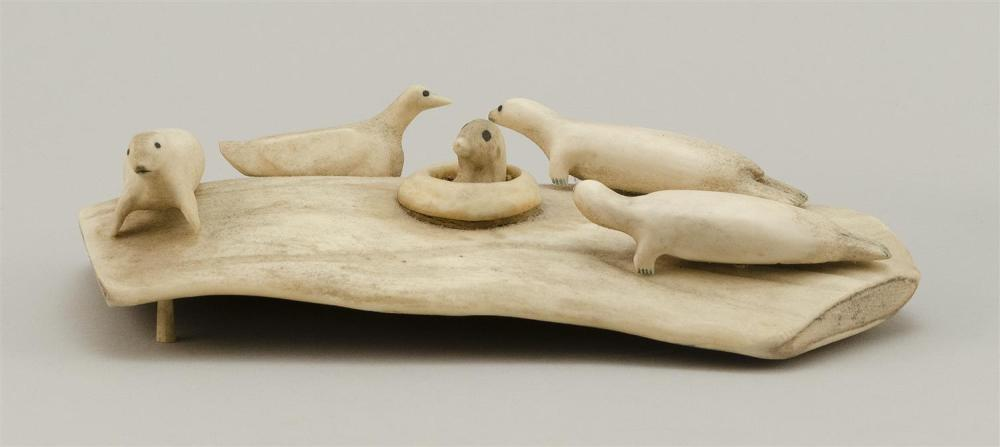 """ESKIMO BONE CARVING OF SEALS Depicts four seals surrounding one whose head is popped up in a hole in the ice. Length 9"""". Width 5.25""""..."""