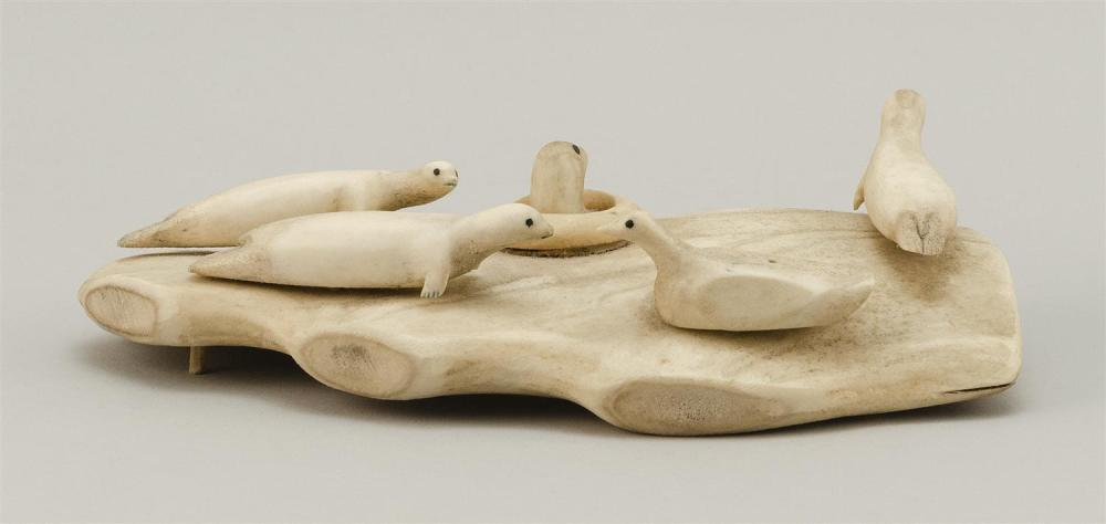 ESKIMO BONE CARVING OF SEALS Depicts four seals surrounding one whose head is popped up in a hole in the ice. Length 9