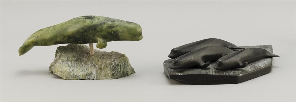 "TWO STONE CARVINGS A green stone narwhal, height 3.75"" and length 7.5"", and a black stone pod of three whales, length 9.75"" and widt..."