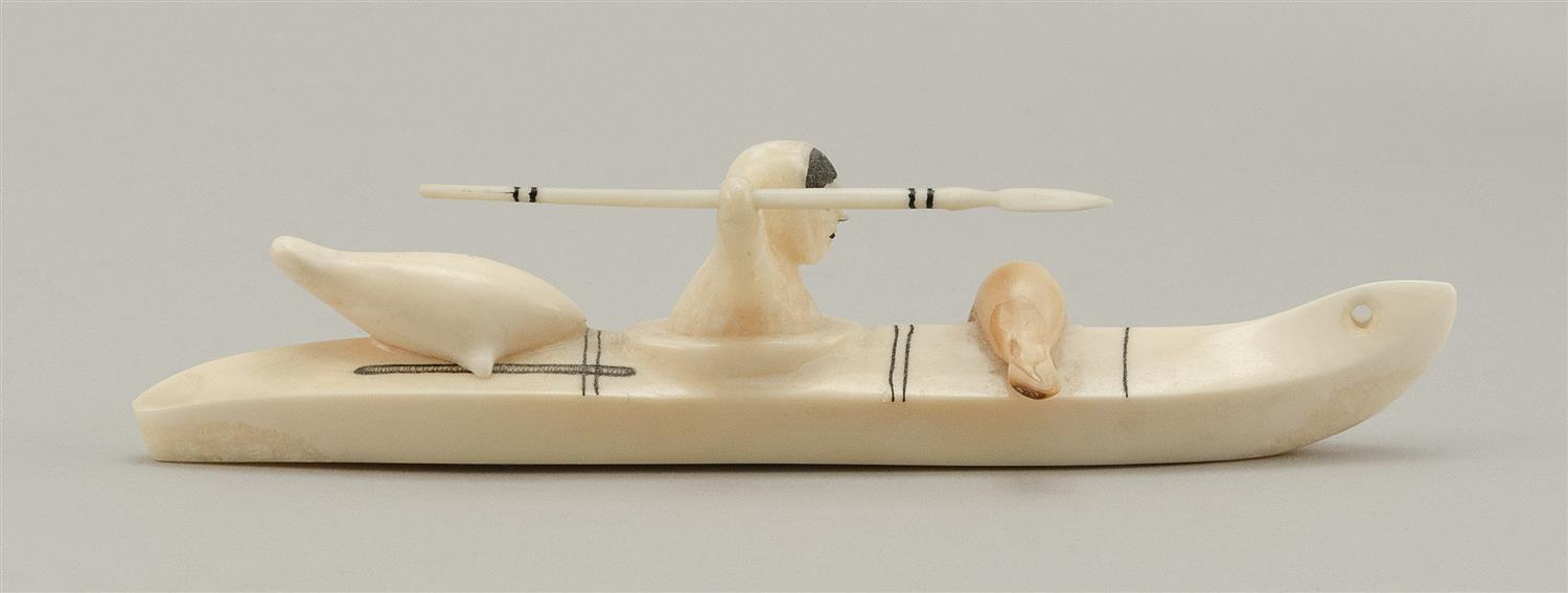 ESKIMO WALRUS IVORY CARVING OF A HUNTER IN A KAYAK With seals on the bow and stern of the kayak, and the hunter poised to throw a ha...