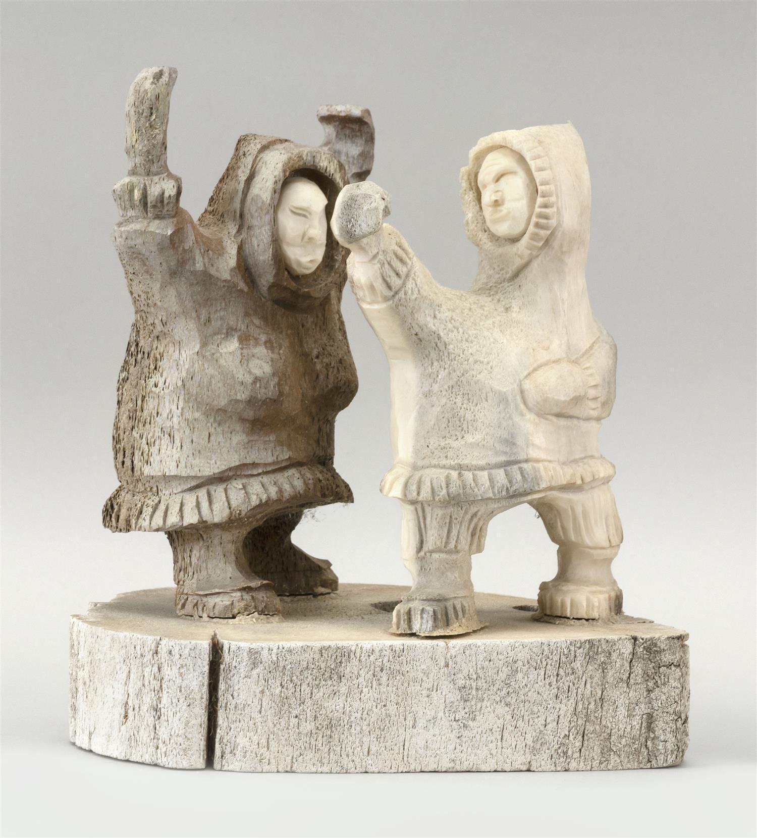 "ALASKAN WHALEBONE CARVING OF TWO ESKIMOS Spirited figures standing on an oval platform. Marked on underside ""Aninga You Nome Alaska""..."