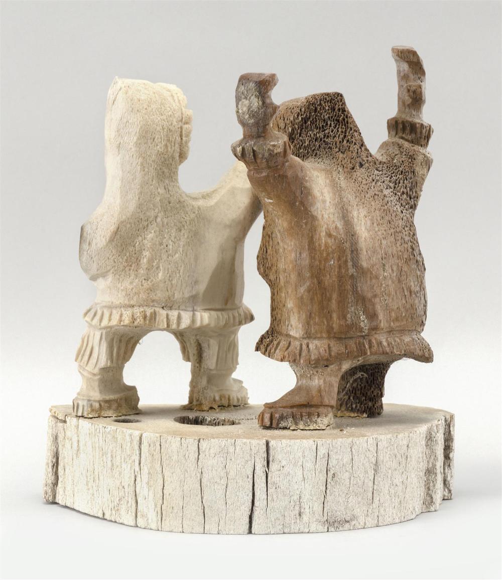 ALASKAN WHALEBONE CARVING OF TWO ESKIMOS Spirited figures standing on an oval platform. Marked on underside