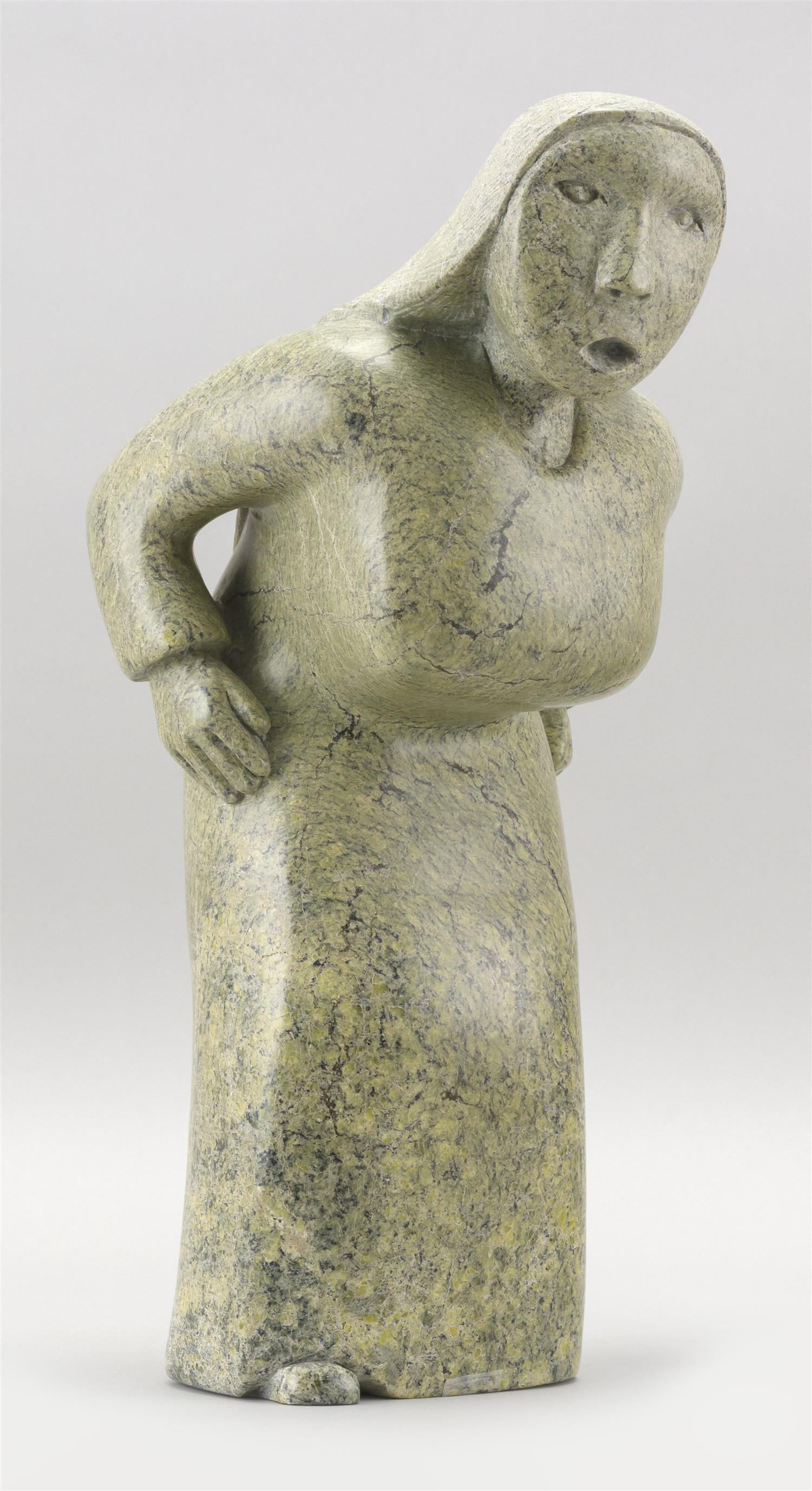 """CAPE DORSET GREEN SOAPSTONE CARVING OF A FEMALE FIGURE Label on underside marked """"Olivoo Tunnillie"""". Height 13.25"""". Proceeds to bene..."""