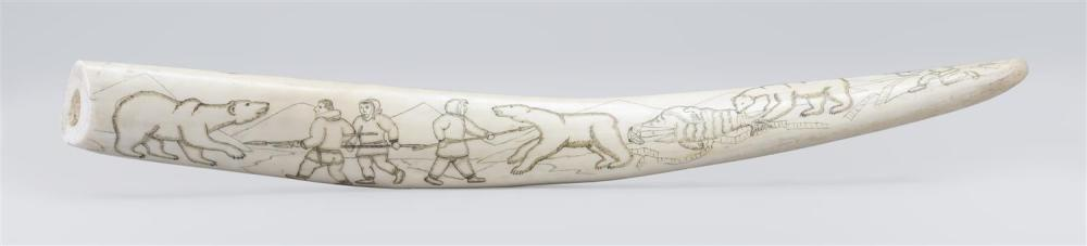 """ENGRAVED WALRUS TUSK Depicts an intricate whaling scene on one face and a polar bear hunt on the other. Signed at base """"Ykomka ...""""...."""