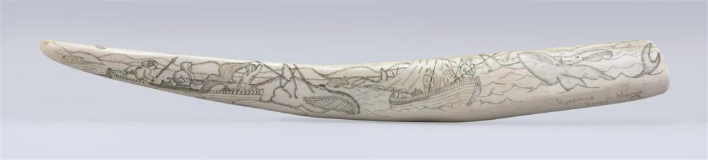 ENGRAVED WALRUS TUSK Depicts an intricate whaling scene on one face and a polar bear hunt on the other. Signed at base