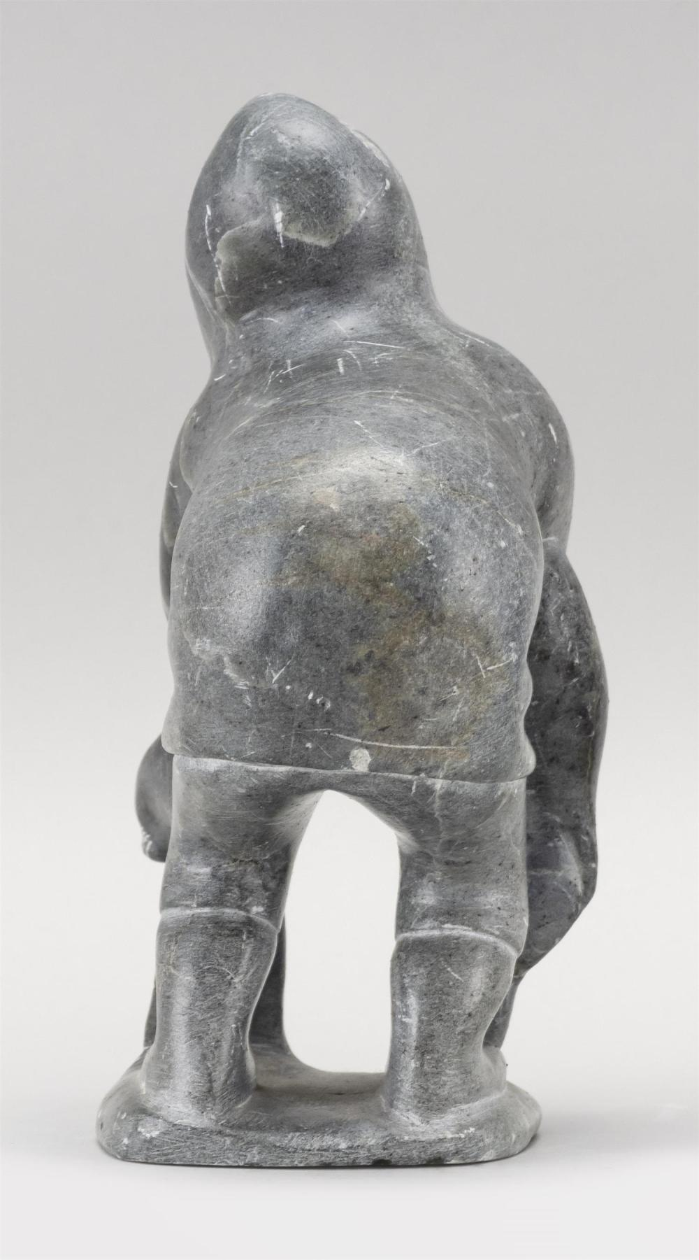 GRAY SOAPSTONE FIGURE OF AN ESKIMO WITH MYTHOLOGICAL SEAL Label on underside marked