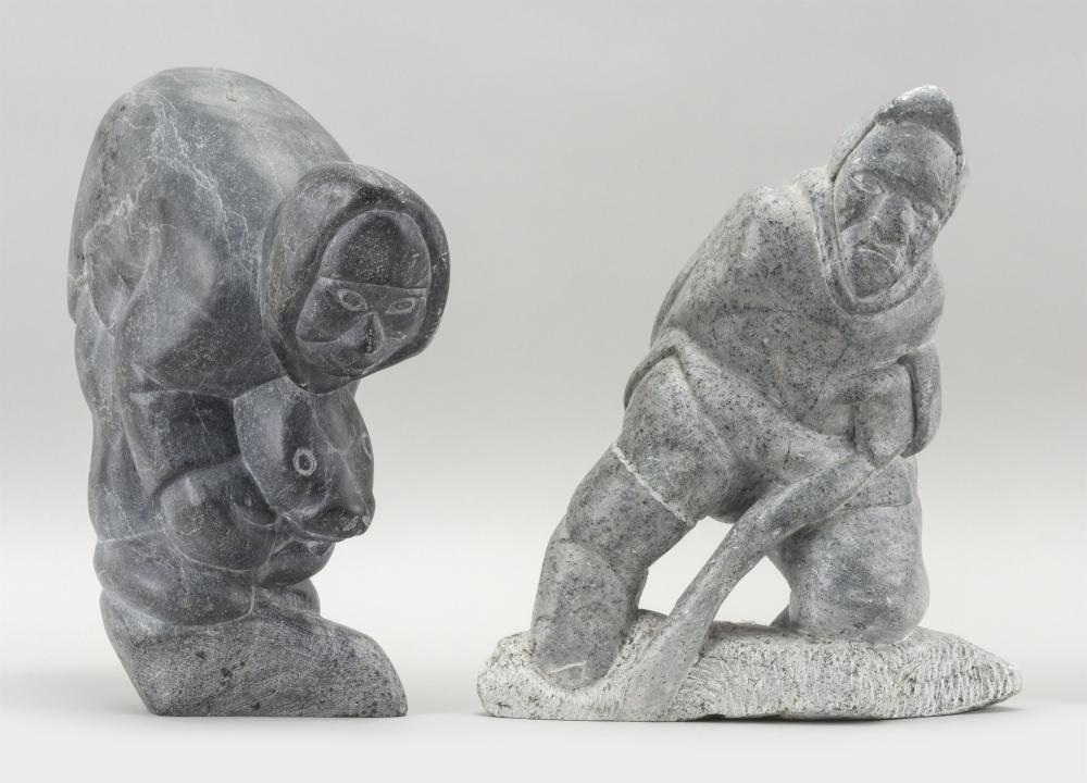 """TWO ESKIMO GRAY SOAPSTONE FIGURAL CARVINGS An Eskimo cutting ice, height 9.5"""", and an Eskimo with a seal, height 10"""". Proceeds to be..."""