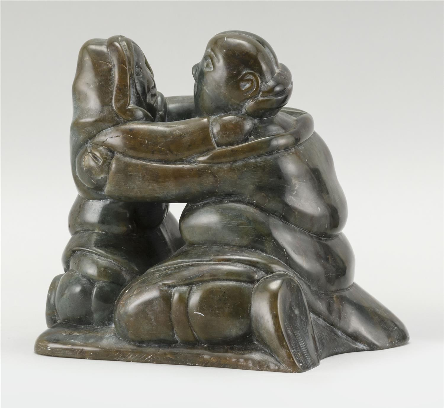 "BROWN AND DEEP GRAY SERPENTINE CARVING OF AN EMBRACING ESKIMO COUPLE Illegibly signed. Height 6"". Proceeds to benefit Cape Symphony..."