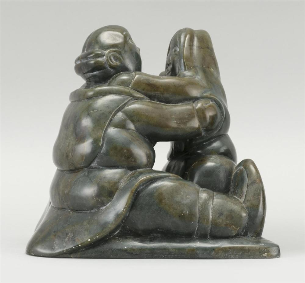 BROWN AND DEEP GRAY SERPENTINE CARVING OF AN EMBRACING ESKIMO COUPLE Illegibly signed. Height 6
