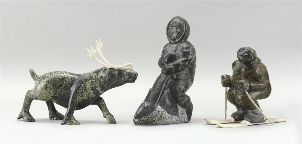 """THREE ESKIMO STONE CARVINGS A soapstone Eskimo with a salmon, height 7.8"""", a green soapstone elk with bone horns, length 8.75"""", and..."""