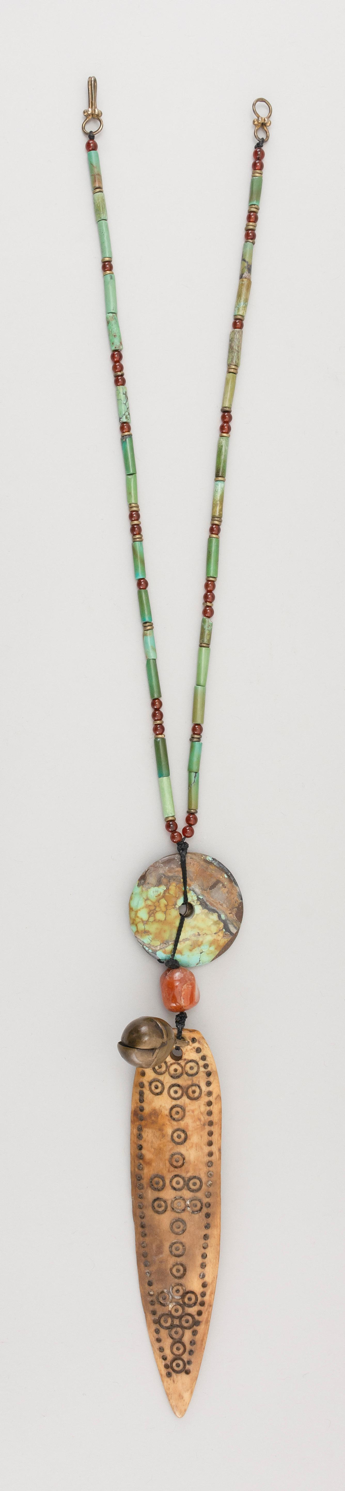 TURQUOISE AND CARNELIAN NECKLACE Unknown date and origin. Suspends a West African coin dated 1926, a turquoise disk and a carved bon...