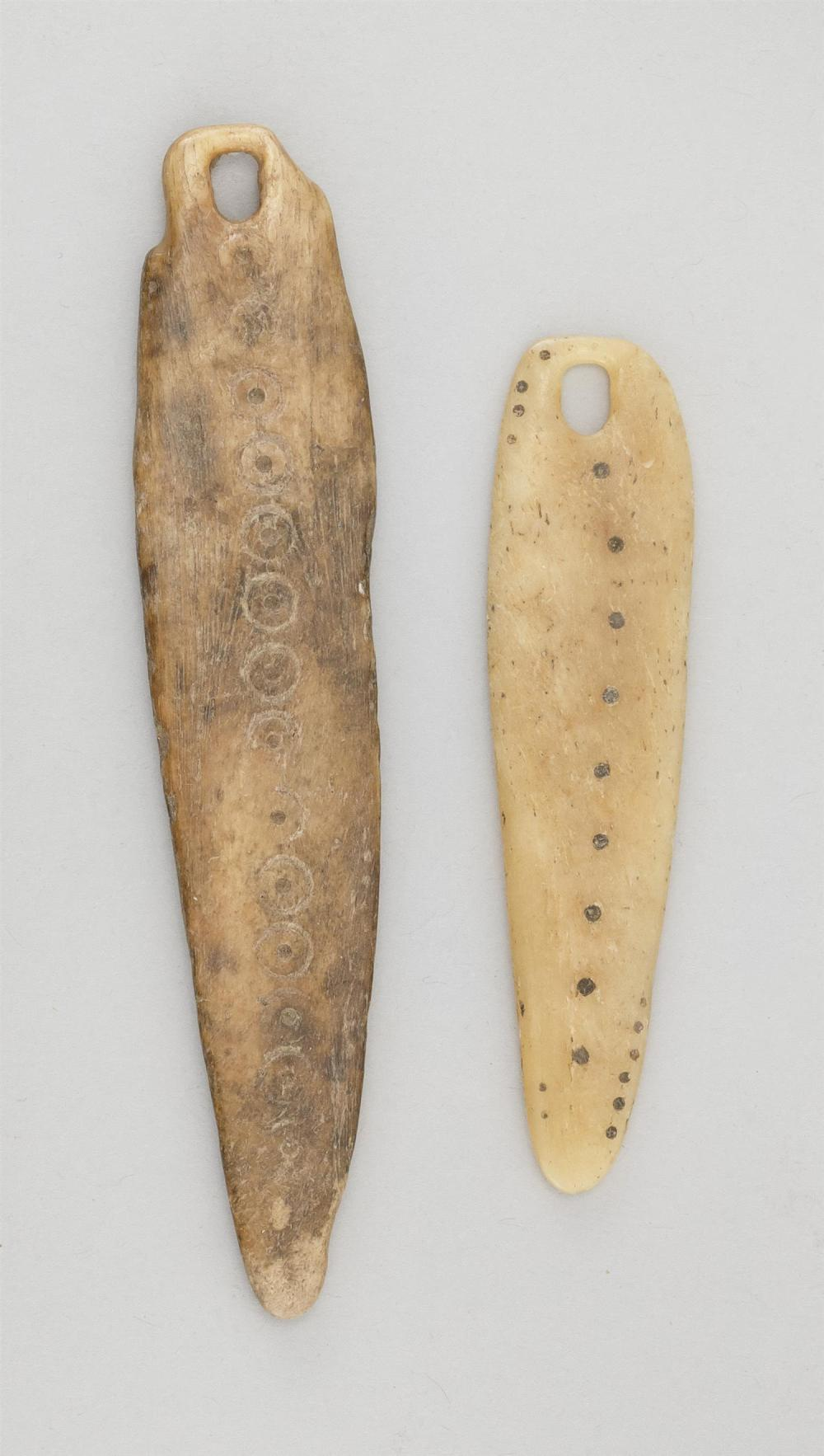 """TWO BONE AMULETS, PROBABLY YUPIK ESKIMO Both with incised circle and dot embellishments. Lengths 3"""" and 4"""". This item is not availab..."""