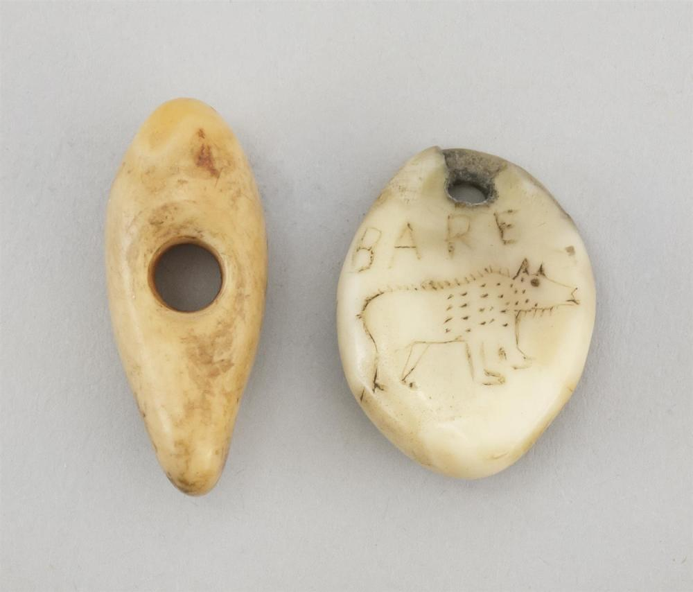 """TWO ESKIMO CARVED BONE AMULETS One in teardrop shape. Other etched """"Bare"""" [sic] above a figure of a bear. Lengths approx. 1"""". This i..."""