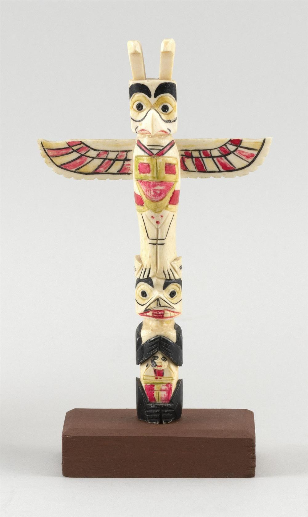 """NORTHWEST COASTAL MINIATURE CARVED AND PAINTED BONE TOTEM POLE With eagle decoration. Height 7"""". Includes wooden base. This item is..."""