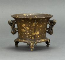 SUNSPOT BRONZE CENSER In squat cylindrical form with slightly flared mouth and fu dog handles. On an elephant's-head-form tri-foot b..