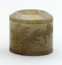 CARVED GRAY AND BROWN JADE ARCHER'S RING In cylindrical form with incised bamboo-carved decoration and calligraphy. Exterior diamete..
