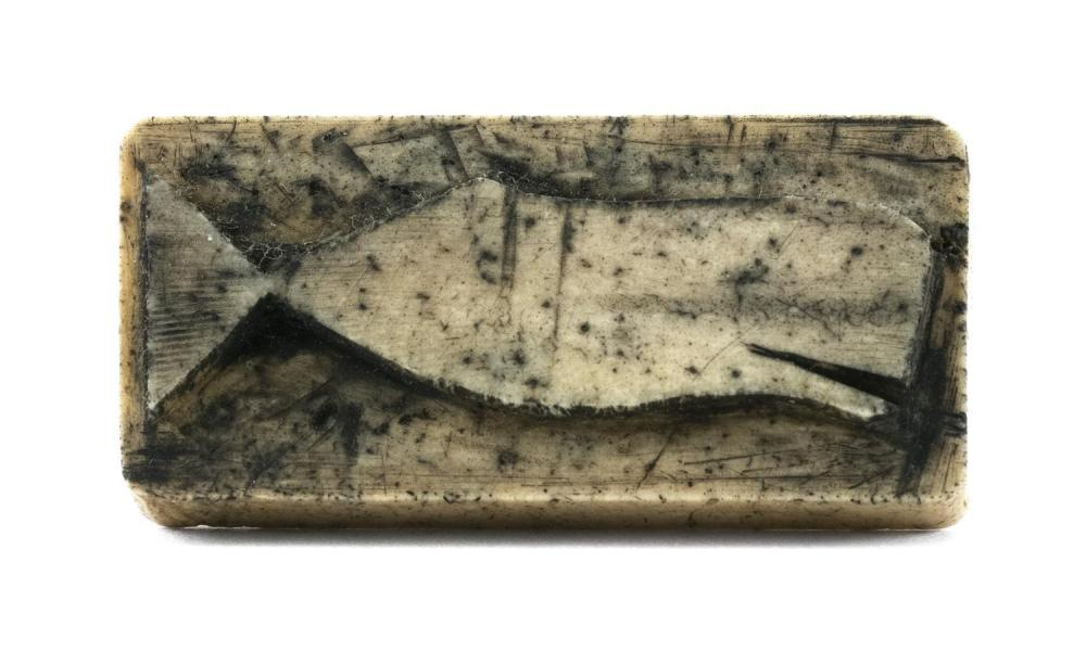 CARVED WHALEBONE LOGBOOK STAMP Stamps an image of a sperm whale. Arched handle with pierced hole. Length 1.13