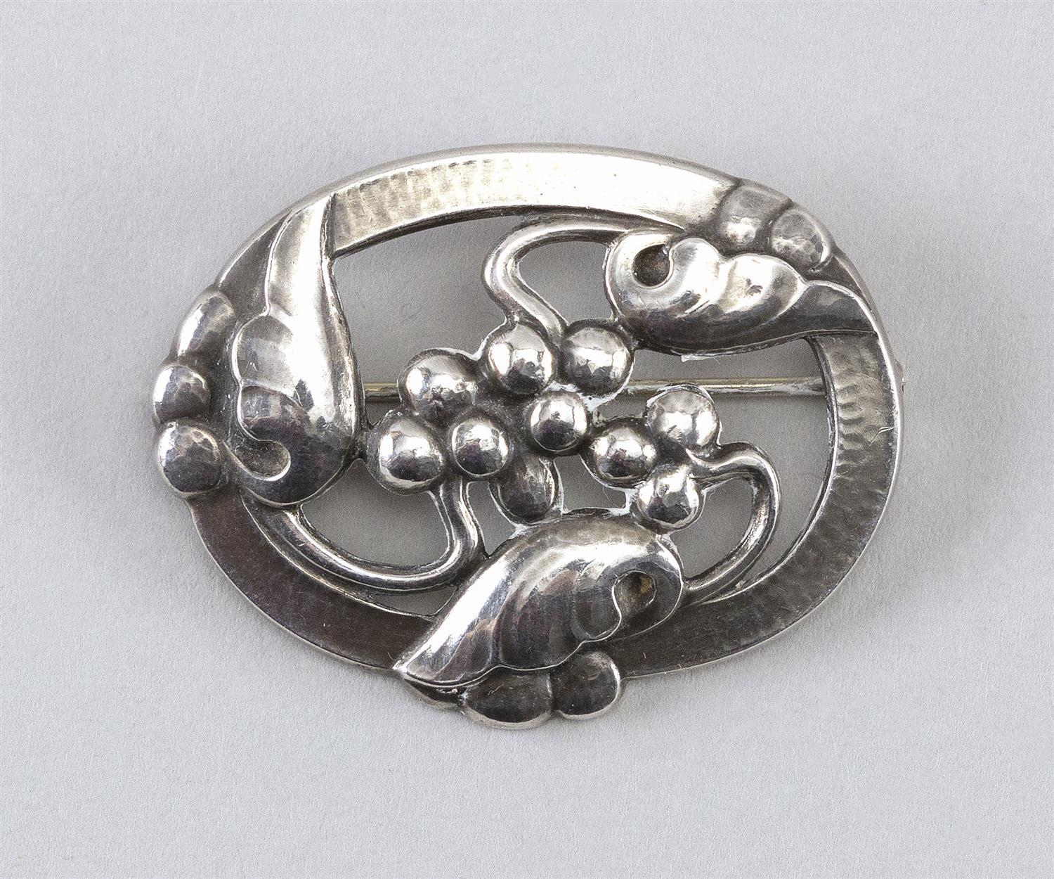 GEORG JENSEN STERLING SILVER BROOCH Numbered 101. Intertwined leaves and berries within an oval frame. Hammered surface. Includes fe...