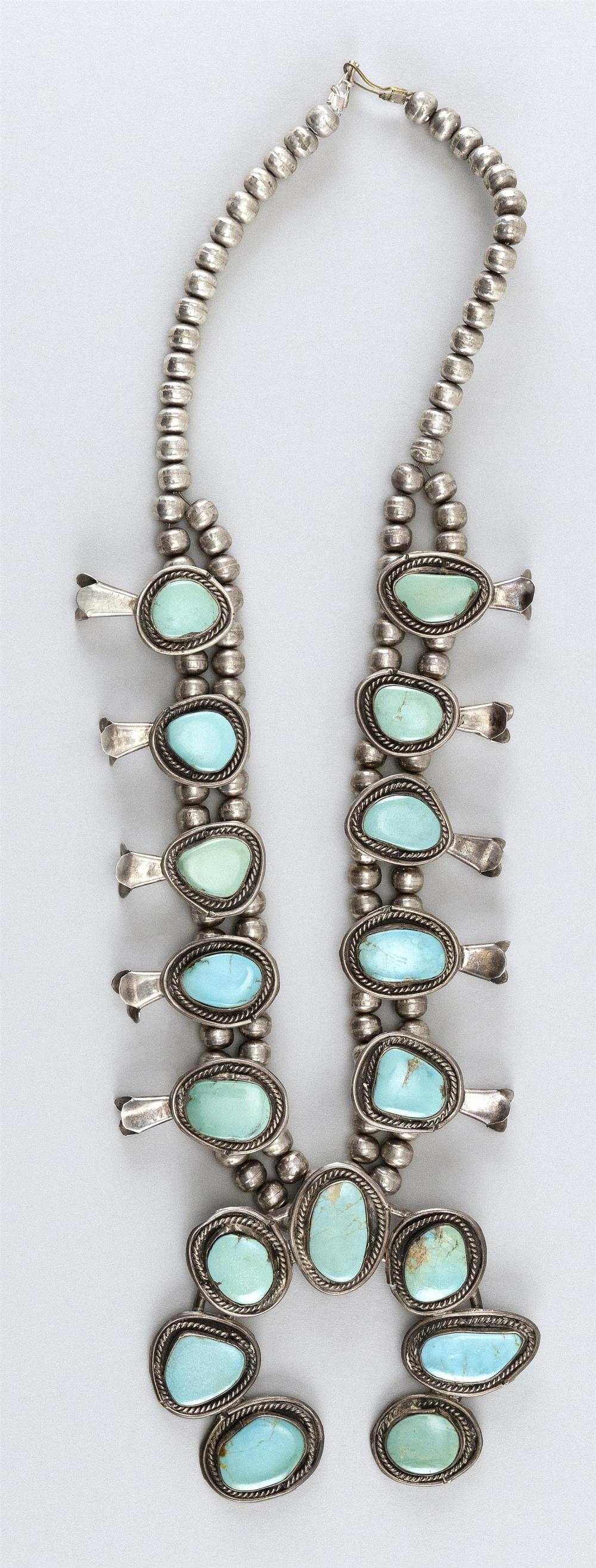 AMERICAN SOUTHWEST INDIAN SILVER AND TURQUOISE SQUASH BLOSSOM NECKLACE Hand-made, but lacking marks. Of typical form, the blossoms a...