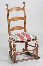 ANTIQUE AMERICAN LADDERBACK ROCKER In maple and oak with turned finials and splintwork seat.