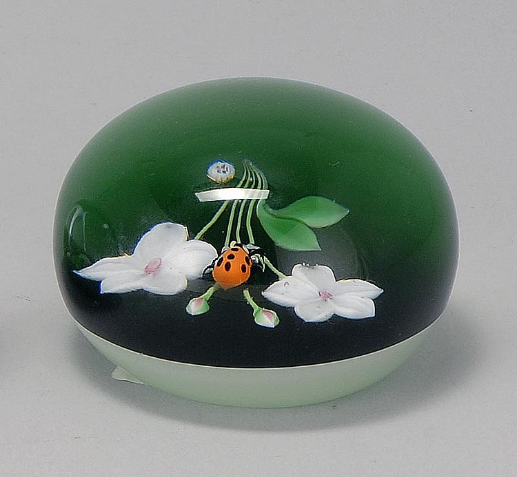 """BACCARAT GLASS PAPERWEIGHT Depicting two flowers and a ladybug. Signed with cane """"1976 B"""". Acid Baccarat signature on bottom. Dated..."""